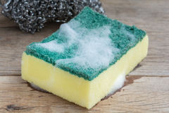 Dishwashing sponge. With foam on wooden background royalty free stock photos
