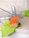 Dishwashing tool on kitchen countertop. Close up of orange sponge and green cloth on the kitchen countertop. Clean sink and faucet in background stock photography