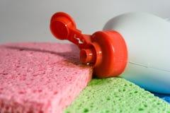Dishwashing vloeistof met veelkleurige sponsen Stock Fotografie
