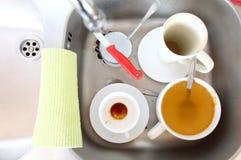 Dishwashing. Witte schotels in de keukengootsteen. stock foto's