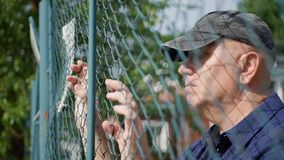Disillusioned Man Image Looking Sad From Back of a Metallic Fence royalty free stock photo