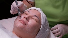 Disincrustation. A woman of Asian appearance on the galvanic cleaning of the face. The work of a beautician with an electrical app. The procedure of stock footage