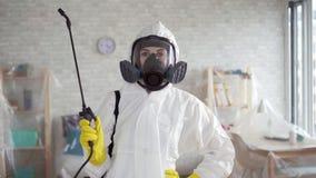Disinfector da jovem mulher ou empresa de limpeza que olham na câmera