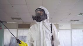 Disinfector in special clothes and a protective mask sprays pesticide