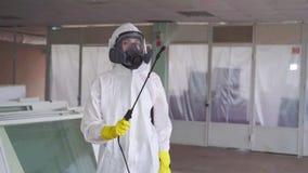 Disinfector in speciale kleren en in een beschermend masker met een spuitbus stock video