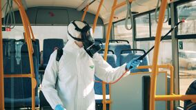 Disinfector is spraying chemical substance on the bus windows