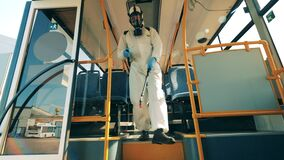 Disinfector is walking along the bus and sanitizing it. Coronavirus prevention, sanitary disinfection process.