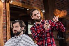 disinfettante di spruzzatura del giovane barbiere sul rasoio diritto fotografie stock