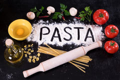 On the disintegrating written flour pasta, tomatoes, mushrooms and herbs. Top view Royalty Free Stock Photo