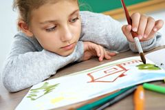 Disinterested young schoolgirl is drawing. Photo of unhappy little girl doing homework. Close up. Education concept Royalty Free Stock Photo
