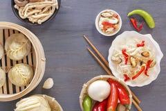 Disk av kinesisk kokkonst i sortiment Ånga klimpar, nudlar, sallader, grönsaker, champinjoner, skaldjur arkivfoto