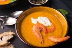2 disk av orange pumpasoppa p? en svart tabell Tre r?da r?kor dekorerar soppan arkivfoton