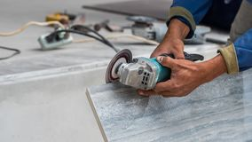 Disk grinder cutting tile in work. In construction site Royalty Free Stock Images