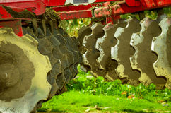 Disk harrow sitting in Green plantation Stock Photo