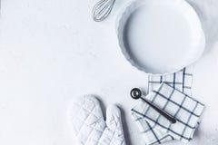 Disk och köktillbehör för att baka på köksbordet på en vit bakgrund arkivfoto