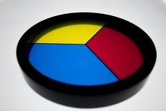 Disk with 3 primary colors, (yellow, blue and red) on a white ba. Ckground with a black border stock photo
