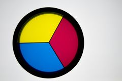 Disk with 3 primary colors, (yellow, blue and red) on a white ba. Ckground with a black border royalty free stock photos