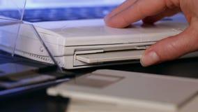 Diskett för diskett för kvinnahandmellanlägg gammal in i bärbar datordatoren lager videofilmer