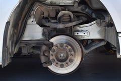 Diskettbroms på bilen, mekaniker som ändrar ett hjul Arkivbild