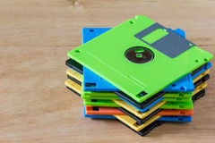 Diskette. Multicolor diskette stacked on wood background stock photography