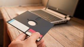 Diskette und Notizbuch auf hölzernem Brett Stockfotografie