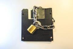 Disketten skyddas av ett lås med en kedja royaltyfri fotografi