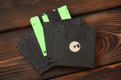 Diskettes y discos en fondo de madera imagen de archivo libre de regalías
