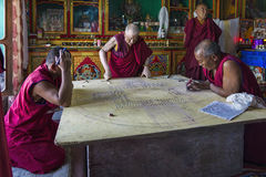 Diskit, India - August 20, 2015: Buddhist monks working on a mandala in monastery prayer hall Stock Images