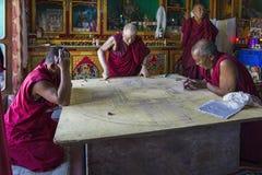 Diskit, la India - 20 de agosto de 2015: Monjes budistas que trabajan en una mandala en pasillo del rezo del monasterio imagenes de archivo