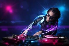 Diskjockey, der Musik mit elektrischen Lichteffekten und Lichtern spielt Lizenzfreie Stockfotografie