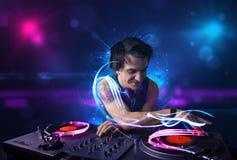 Diskjockey, der Musik mit elektrischen Lichteffekten und Lichtern spielt Stockfotos