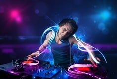 Diskjockey, der Musik mit elektrischen Lichteffekten und Lichtern spielt Stockfotografie