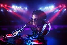 Diskjockey, der Musik mit Lichtstrahleffekten auf Stadium spielt Lizenzfreies Stockfoto