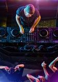 Diskjockey som blandar elektronisk musik i klubba royaltyfri bild