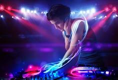 Diskjockey som spelar musik med effekter för ljus stråle på etapp Arkivfoto