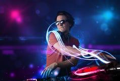 Diskjockey som spelar musik med electro ljusa effekter och ljus Arkivbilder