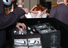 Diskjockey at wedding. Bride and guests dancing to the diskjockey's selection of a lively tune Stock Image