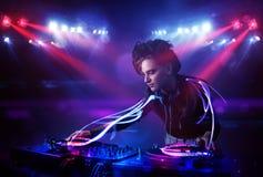 Diskjockeyflicka som spelar musik med effekter för ljus stråle på etapp arkivfoto
