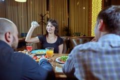 Diskussion av tre ilskna vänner som argumenterar i en coffee shop arkivfoto