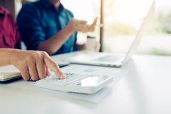 Diskussionsanalyse mit zwei Geschäftsmännern, die zusammen Berechnungen über das Firmenbudget und Finanzplanung auf Schreibtisch  stockfotografie