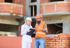 diskutera plan Den kvinnateknikern och byggmästaren meddelar på konstruktionsplatsen Begrepp för konstruktionslagkommunikation arkivbild