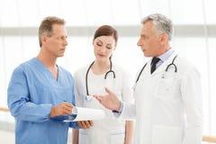 Diskutera rapporten. Sjukhusdoktorer som diskuterar patienten Arkivfoto