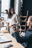 Diskutera riskabla idéer Tre unga affärspersoner som diskuterar s Arkivfoton