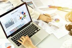 Diskuterar granskar upptaget arbete för kontorsarbetare, planläggningen för affärsstrategi, affärskvinnor och datadokument arkivfoton