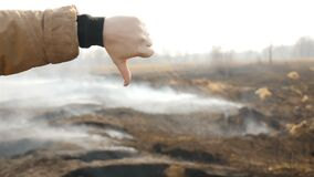 Dislike on the background of a field with smoke. Atmospheric pollution. Ecological catastrophy. Slow motion. Close-up