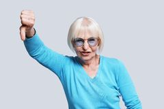 Dislike!. Playful senior woman making dislike gesture while standing against grey background royalty free stock images