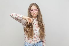 Dislike sign. Beautiful girl demonstrating dislike. Studio shot, gray background royalty free stock photos