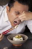 Dislike tofu. A man squeeze his nose dislike habit in a dish of Japanese soft tofu Royalty Free Stock Photos