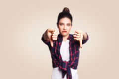 Dislike. Young unhappy upset girl with casual style and bun hair thumbs down her finger, on beige blank wall with copy space. Looking at camera with toothy Stock Image