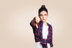 Dislike. Young unhappy upset girl with casual style and bun hair thumbs down her finger, on beige blank wall with copy space Royalty Free Stock Images